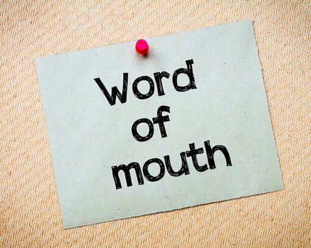 referrer: Word of mouth Message. Recycled paper note pinned on cork board. Concept Image