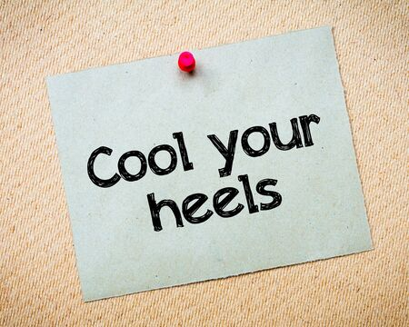 no heels: Cool your heels Message. Recycled paper note pinned on cork board. Concept Image