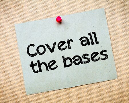bases: Cover all the bases Message. Recycled paper note pinned on cork board. Concept Image