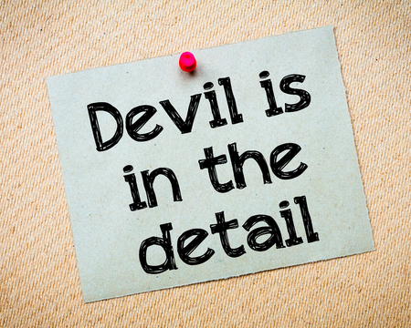 red devil: Devil is in the detail Message. Recycled paper note pinned on cork board. Concept Image