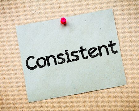 Consistent Message. Recycled paper note pinned on cork board. Concept Image