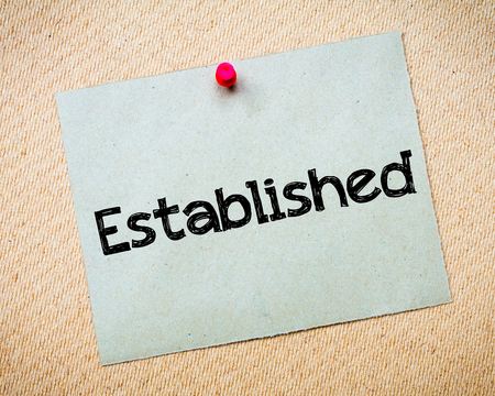 established: Established Message. Recycled paper note pinned on cork board. Concept Image Stock Photo