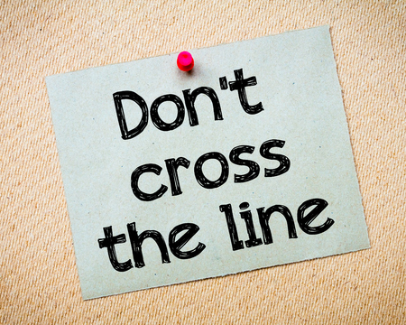unacceptable: Dont cross the line Message. Recycled paper note pinned on cork board. Concept Image