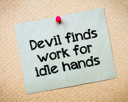 finds: Devil finds work for idle hands Message. Recycled paper note pinned on cork board. Concept Image