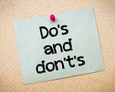 Dos and Donts Message. Recycled paper note pinned on cork board. Concept Image