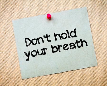 Dont hold your breath Message. Recycled paper note pinned on cork board. Concept Image