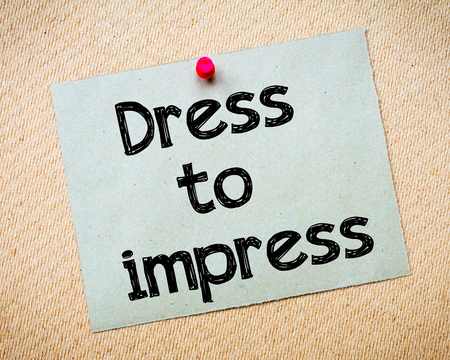 impress: Dress to impress Message. Recycled paper note pinned on cork board. Concept Image