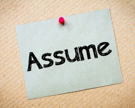 assume: Assume Message. Recycled paper note pinned on cork board. Concept Image