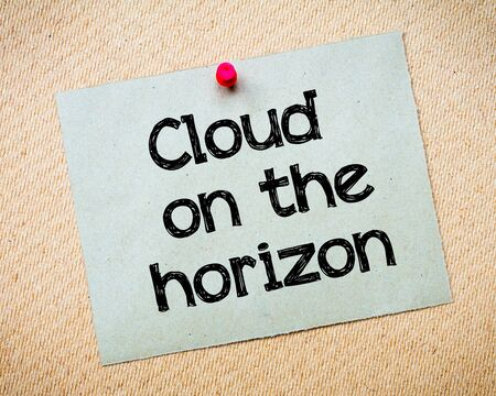 idioms: Cloud on the horizon Message. Recycled paper note pinned on cork board. Concept Image