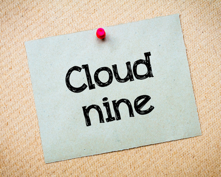 on cloud nine: Cloud Nine Message. Recycled paper note pinned on cork board. Concept Image