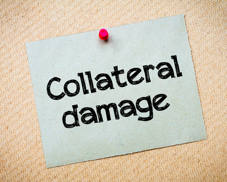 collateral: Collateral Damage Message. Recycled paper note pinned on cork board. Concept Image