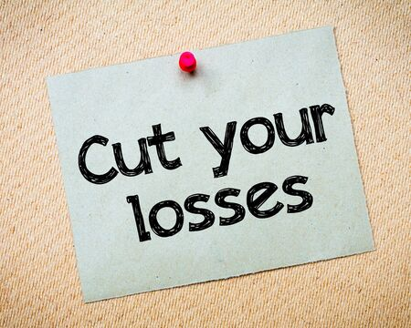 idioms: Cut your losses Message. Recycled paper note pinned on cork board. Concept Image Stock Photo