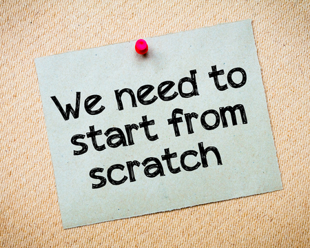idioms: We need to start from scratch Message. Recycled paper note pinned on cork board. Concept Image