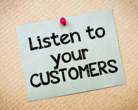 idioms: Listen to your customers Message. Recycled paper note pinned on cork board. Concept Image