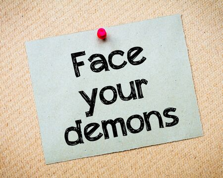 idioms: Face your demons Message. Recycled paper note pinned on cork board. Concept Image