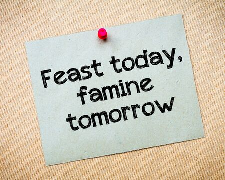 Feast today, famine tomorrow Message. Recycled paper note pinned on cork board. Concept Image