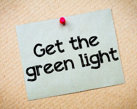 idioms: Get the Green Light Message. Recycled paper note pinned on cork board. Concept Image