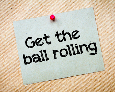 Get the ball rolling Message. Recycled paper note pinned on cork board. Concept Image photo
