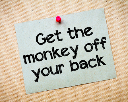 Get the monkey of your back Message. Recycled paper note pinned on cork board. Concept Image