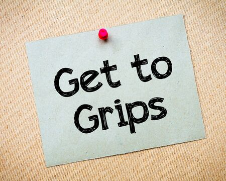 idioms: Get the grips Message. Recycled paper note pinned on cork board. Concept Image Stock Photo