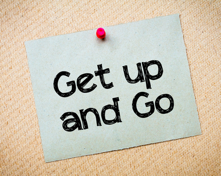 idioms: Get up and Go Message. Recycled paper note pinned on cork board. Concept Image Stock Photo