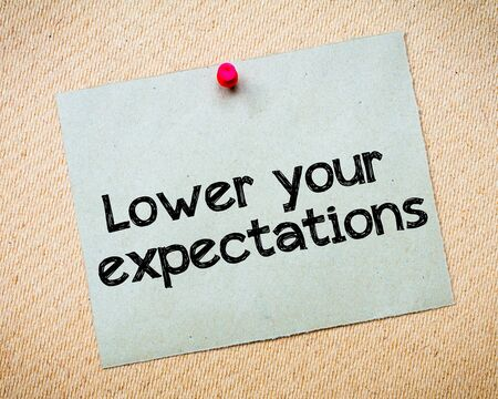 Lower your expectations Message. Recycled paper note pinned on cork board. Concept Image