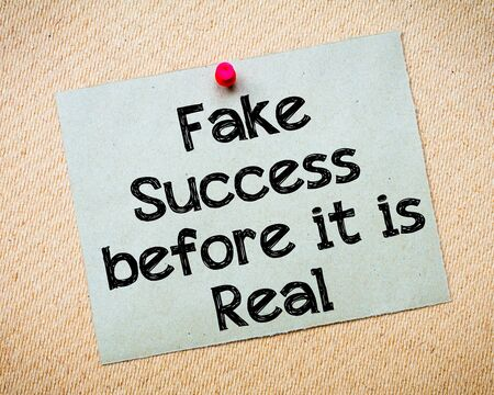 idioms: Fake success before it is real Message. Recycled paper note pinned on cork board. Concept Image