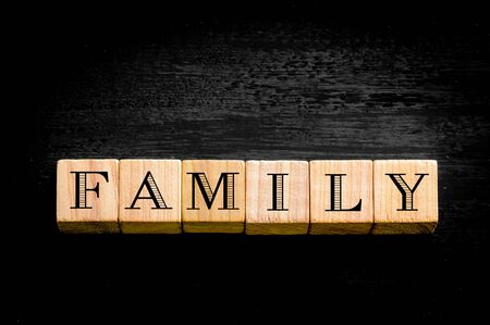 familiy: Wooden small cubes with letters isolated on black background. Stock Photo
