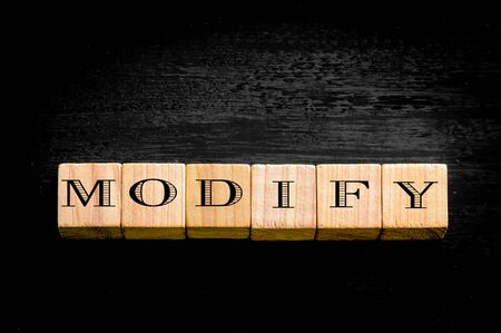 modify: Word Modify. Wooden small cubes with letters isolated on black background.Concept image. Stock Photo