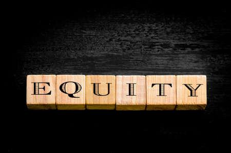 equidad: Palabra Equidad. Peque�os cubos de madera con letras aisladas imagen background.Concept negro sobre. Foto de archivo
