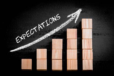 黒の背景に分離された木製つみきのバー グラフの上の矢印を昇順に単語の期待。