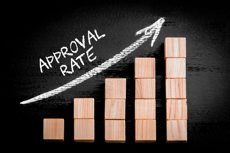 approval rate: Word Approval Rate on ascending arrow above bar graph of Wooden small cubes isolated on black background.