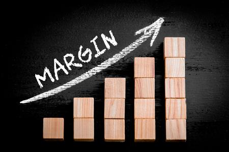 margin: Margen Word en ascendente flecha encima de gr�fico de barras de peque�os cubos de madera aisladas sobre fondo negro. Foto de archivo