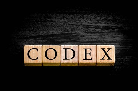 codex: Word CODEX. Wooden small cubes with letters isolated on black background with copy space available. Concept image.