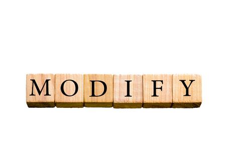 modificar: Palabra MODIFICAR. Pequeños cubos de madera con las cartas aisladas sobre fondo blanco con espacio de copia disponible. Concepto de imagen.