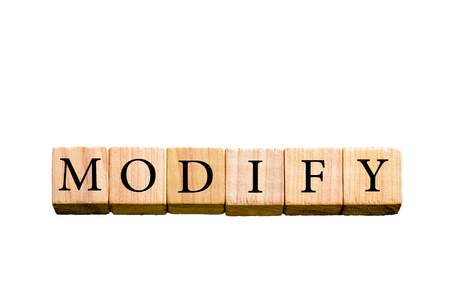 modify: Word MODIFY. Wooden small cubes with letters isolated on white background with copy space available. Concept image. Stock Photo