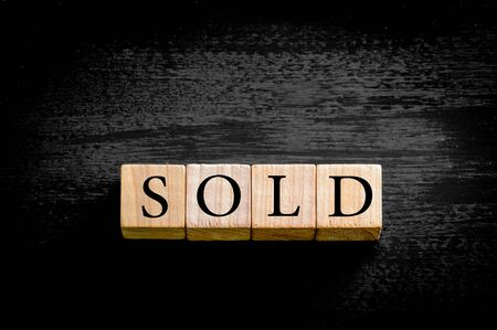 sold small: Word SOLD. Wooden small cubes with letters isolated on black background with copy space available. Concept image.
