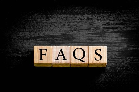 faq's: Word FAQS. Wooden small cubes with letters isolated on black background with copy space available. Concept image. Stock Photo