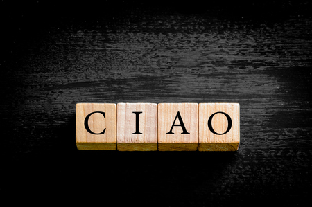 ciao: Word CIAO. Wooden small cubes with letters isolated on black background with copy space available. Concept image. Stock Photo
