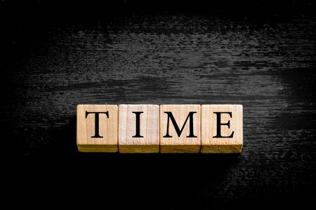 available time: Word TIME. Wooden small cubes with letters isolated on black background with copy space available. Concept image.