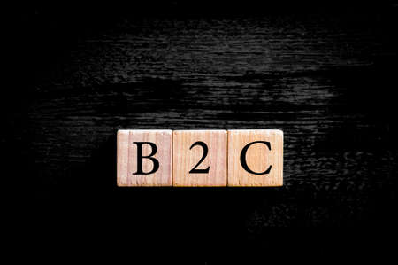 b2c: Acronym B2C- Business to Consumer. Wooden small cubes with letters isolated on black background with copy space available.Business Concept image.