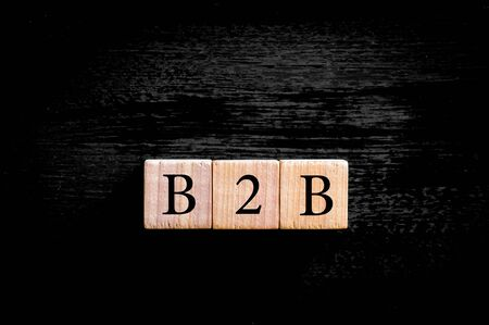 b2b: Acr�nimo B2B- Business to Business. Peque�os cubos de madera con las cartas aisladas sobre fondo negro imagen copia espacio available.Business Concepto con.