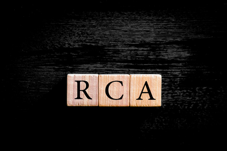 rca: Acronym RCA - Root cause analysis. Wooden small cubes with letters isolated on black background with copy space available. Business Concept image.