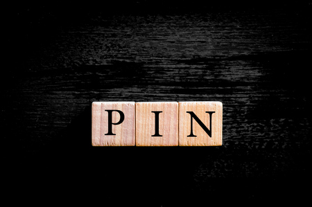 personal identification number: Word PIN -Personal identification number.  Wooden small cubes with letters isolated on black background with copy space available. Business Concept image.