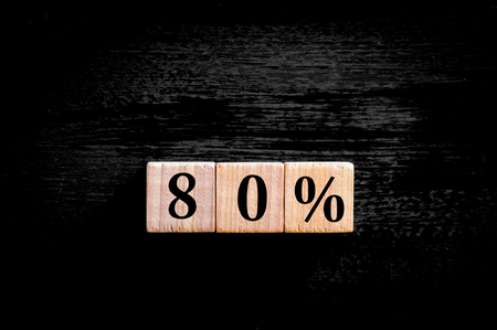 eighty: Eighty percent symbol. Wooden small cubes with letters isolated on black background with copy space available. Concept image. Stock Photo
