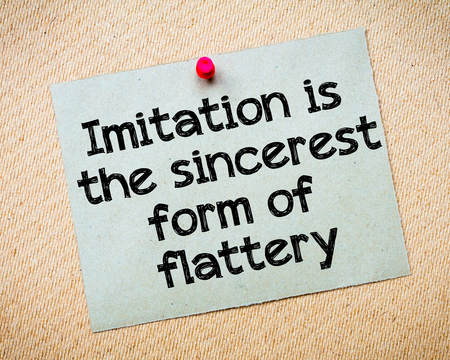 sincere: Imitation is the sincere form of flattery Message. Recycled paper note pinned on cork board. Concept Image