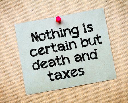 muerte: Nada es seguro sino la muerte y los impuestos del mensaje. Reciclado nota de papel clavado en tarjeta del corcho. Concepto de imagen