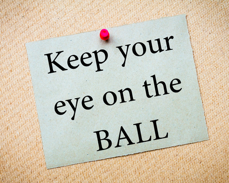 keep an eye on: Keep Your Eye On The Ball Message. Recycled paper note pinned on cork board. Concept Image Stock Photo