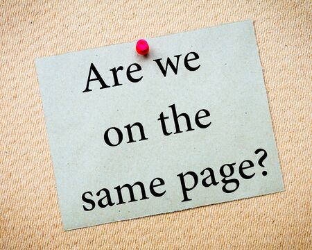 idioms: Are We On The Same Page? Message. Recycled paper note pinned on cork board. Concept Image