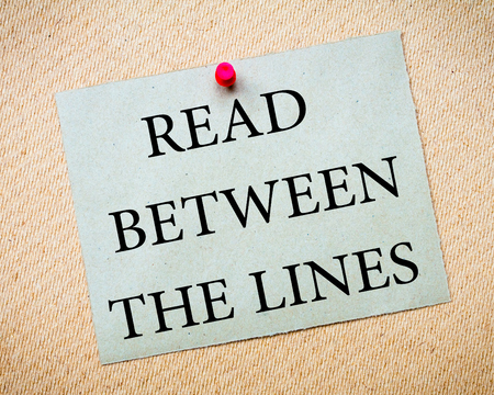 metaphoric: Read Between The Lines Message. Recycled paper note pinned on cork board. Concept Image